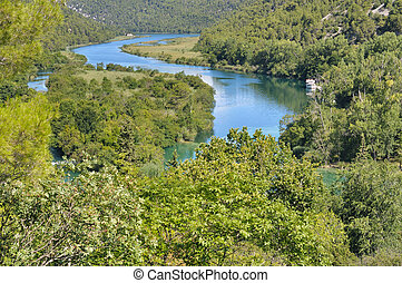 park in croatia Krka - River passing through a lush forest...