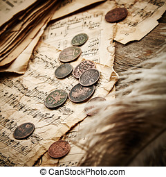 Vintage still life with ancient coins and music sheets on...