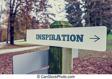Inspiration signboard on a wooden post with a right pointing...