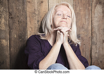 A senior person pray with a wood background