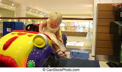 blonde girl climbs out the toy car herself - little blonde...