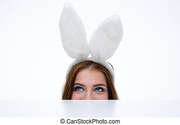 Woman with bunny ears looking over table