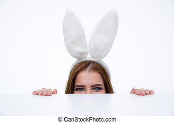 Woman with bunny ears looking over table at the camera