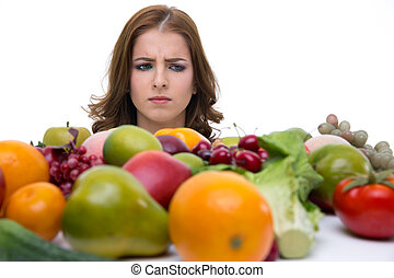 Portrait of a pensive woman looking on the fruits