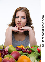 Portrait of a serious woman sitting at the table with fruits