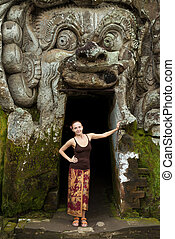 Young woman standing at Goa Gajah - Young woman standing in...