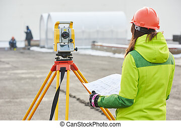 surveyor works with theodolite - female surveyor worker...