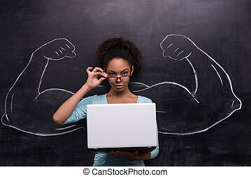 Afro-american woman with laptop and painted muscular arms on...