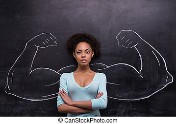 Serious afro-american woman with painted muscular arms on...