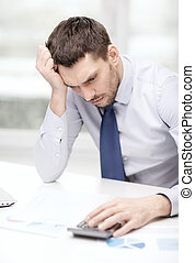 stressed businessman with laptop and documents - office,...