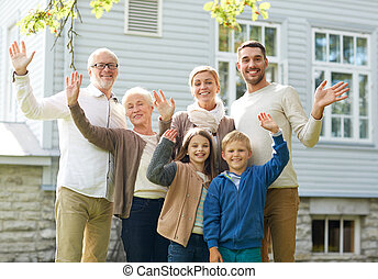 happy family waving hands in front of house - gesture,...