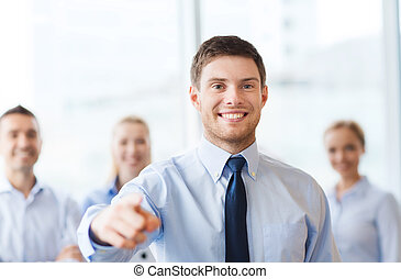 smiling businessman with colleagues in office - business,...