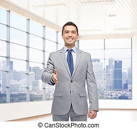 happy smiling businessman in suit shaking hand - business...