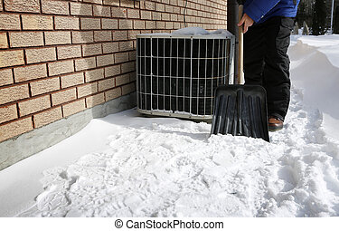 AC under show - Man shoveling the show with brick wall and...