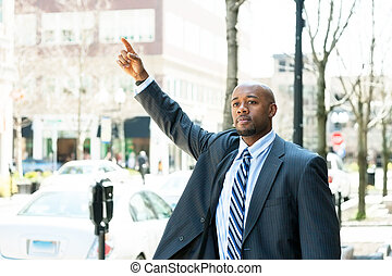 Man Hailing a Taxi Cab - An African American business man...