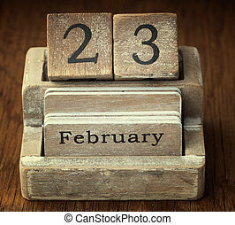 A very old wooden vintage calendar showing the date 23rd...