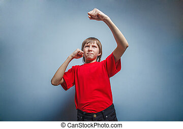 Boy, teenager, twelve years red in shirt, showing his fists...