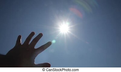 Man`s hand playing to the sun at dawn