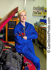 woman as a mechanic in auto repair shop - a young woman as a...