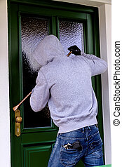 burglar at a house door - a burglar trying to break a door.