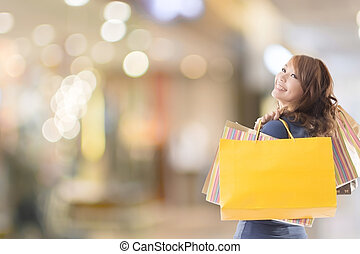 Cheerful shopping woman of Asian holding bags