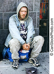 Outcast - An homeless person is sitting on his backpack.