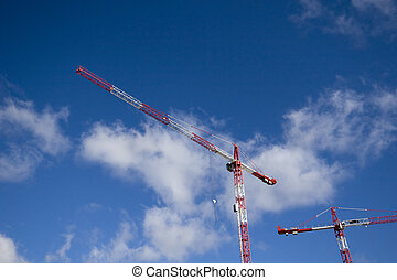 Cranes - Alternately red and white construction cranes on...