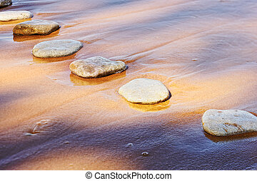 Sand and Stones - Several flat boulder in the wet sand
