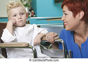 An adorable little boy in the wheelchair at the hospital with do