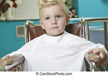 An adorable little boy in the wheelchair at the hospital