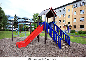 red and blue playground outside apartment buildings
