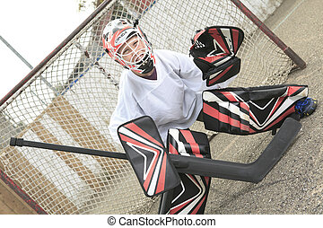A young teen hockey goaler outside in the arena