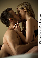 Hugging in bed - Young sexy passionate couple hugging in bed