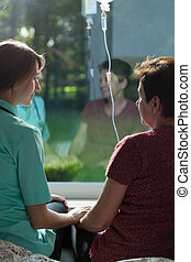 Ill woman talking with kindly nurse - Ill woman sitting on...