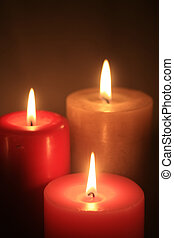 group of three burning candles - Three burning candles in a...