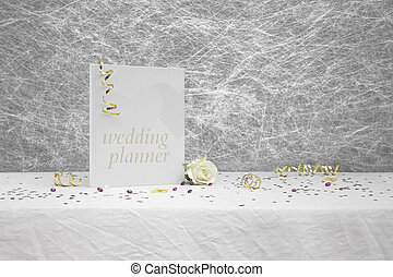 Wedding planner book on a White tablecloth with gold ribbons,bow