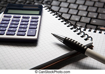pen with calculator on a notebook and keyboard close up