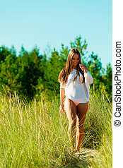 woman walking on grassy dune - Beautiful young woman...