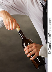 Man opening bottle of wine - Man waiter opening bottle of...