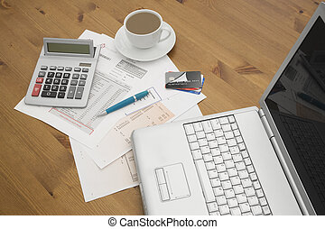 credit cards on a laptop with credit card statements a cup...
