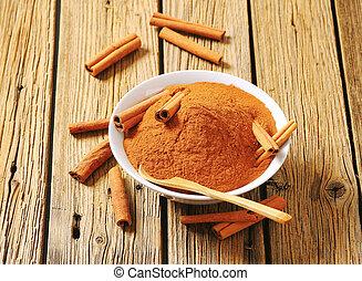 Bowl of ground cinnamon and cinnamon sticks