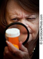 Woman examining medicine bottle - Woman closely examining...