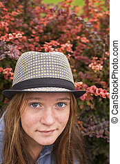 Young lovely girl in a hat, close-up portrait of a spring garden.