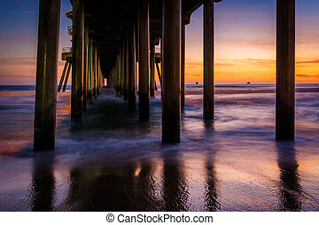 Under the pier at sunset, in Huntington Beach, California.