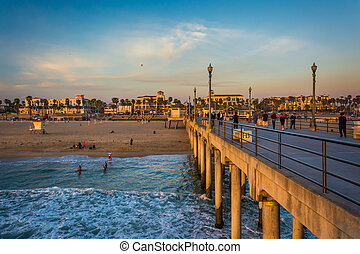 The pier and view of the beach at sunset, in Huntington Beach, C