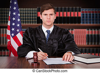 Male Judge Sitting In Courtroom - Portrait Of Young Male...