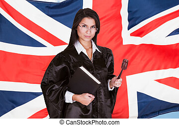 Portrait Of Female Judge With Book And Gavel Standing In...