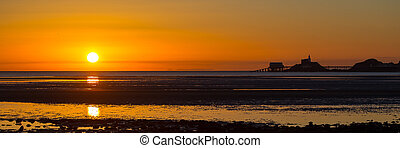 Mumbles sunrise panorama - The sun rises over a wide expanse...