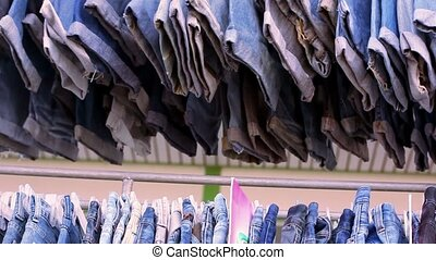 Close up of many blue jeans hanging on a rail Video macro...