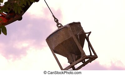 Industrial Crane operating and lifting cement tank against sky. Video